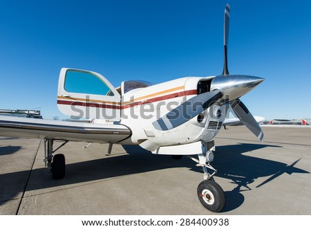 propeller aeroplane standing on asphalt landing runway - stock photo
