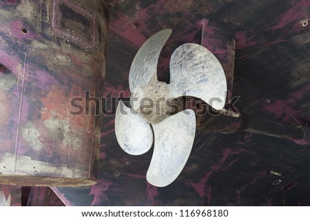 Propeller and rudder of vessel in dry dock - stock photo