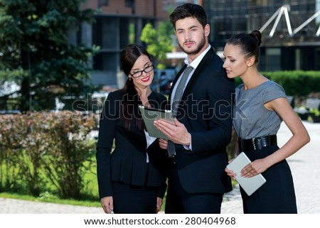 Proper business agreement. Three confident and motivated business partners are looking in tablet and discussing issues of business project. All are wearing formal suits. Outdoor business concept - stock photo