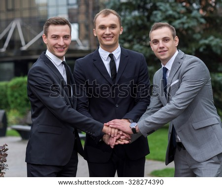 Proper business agreement. Three  confident and motivated business partners are shaking hands while discussing issues of business project. All are wearing formal suits. Outdoor business concept - stock photo