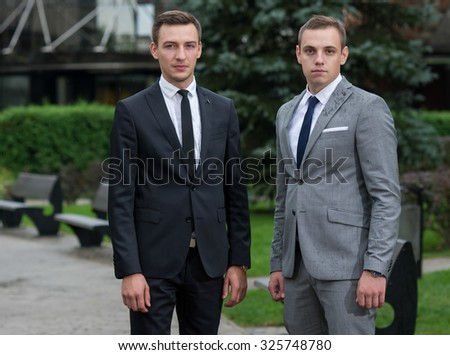 Proper business agreement. Two  confident and motivated business partners are watching in tablet and discussing issues of business project. All are wearing formal suits. Outdoor business concept - stock photo