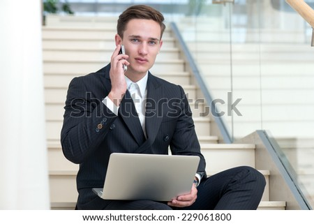 Proper business decisions by the mobile phone. Motivated businessman is sitting with mobile phone and laptop and doing his important business doings - stock photo