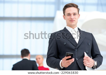 Proper deal. Young and motivated businessman is smiling directly to the camera, while standing with tablet. Two his colleagues are standing on the background and discussing important business stuff. - stock photo