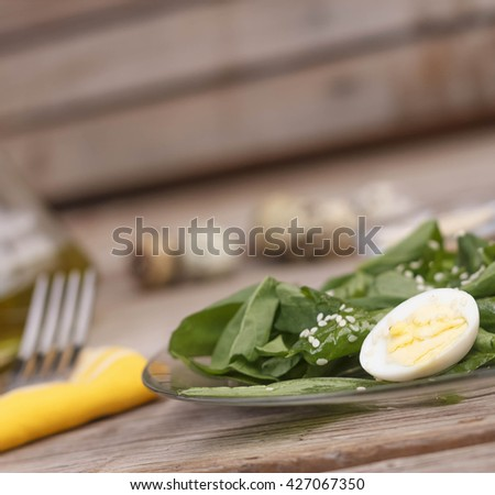 Proper nutrition. Diet, weight loss. Spinach salad with quail eggs. Closeup - stock photo