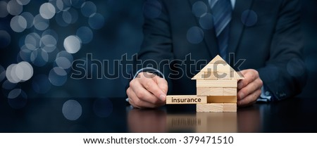 Property (family house) insurance protection concept. Insurance agent complete wooden model of the house with last piece with text insurance. Wide banner composition with bokeh background.  - stock photo