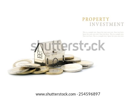 property investment, silver golden house model on coins isolated on white background, copy space with sample text