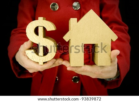 property purchase, woman holding golden house and a golden dollar symbol - stock photo