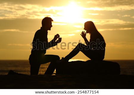 Proposal on the beach with a man silhouette asking for marry at sunset with the sun in the background - stock photo