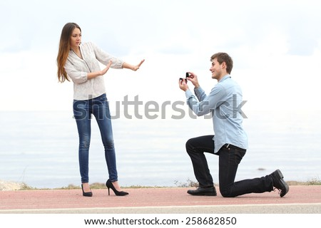 Proposal rejection when a happy man asks in marriage to a woman on the beach
