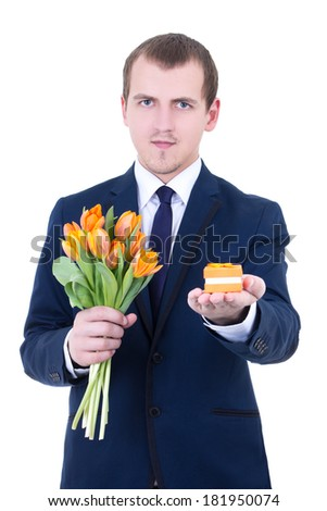 proposal - young man in suit holding gift box with wedding ring and flowers isolated on white background - stock photo