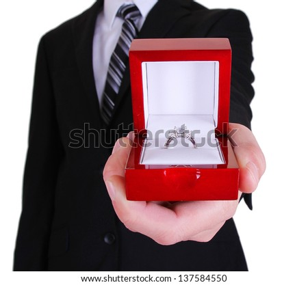 proposing man and engagement ring holding up with box isolated on white background - stock photo