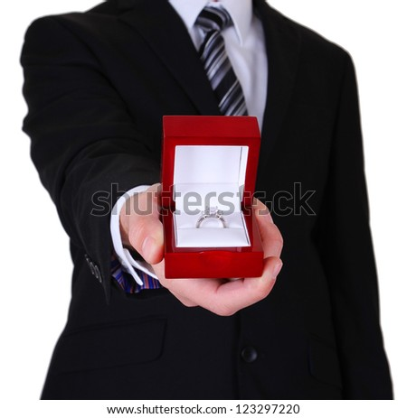 proposing man and holding up an engagement ring with box isolated on white background - stock photo