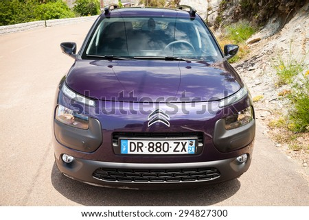 Propriano, France - July 1, 2015: Dark purple new Citroen C4 Cactus on the mountain road of Corsica - stock photo