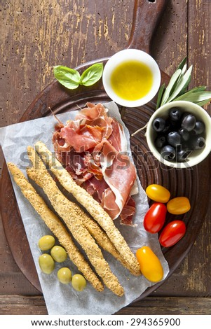 prosciutto crudo on a wooden board. Serving a snack. olives, tomatoes, olive oil. breadsticks. Natural Health Food Italy - stock photo