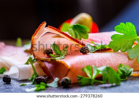 Prosciutto. Curled Slices of Delicious Prosciutto with parsley leaves on granite board. Prosciutto with spice cherry tomatoes garlic and olive. Italian and Mediterranean cuisine  - stock photo