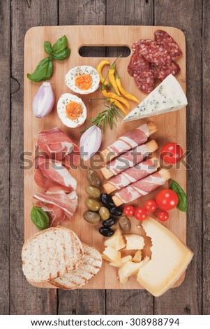 Prosciutto di Parma with olives and other italian antipasto food - stock photo