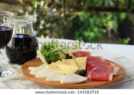 Prosciutto, homemade cheese, cheese, cured meats and clotted cream on wooden board. Traditional Balkan, Italian, chernogoskoe dish. Montenegrin appetizer. - stock photo
