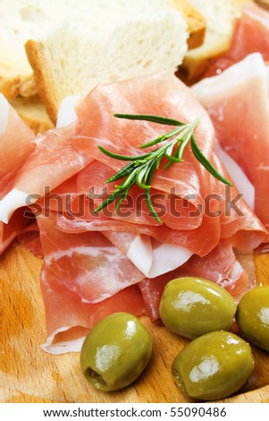 Prosciutto, italian cured ham, with bread and green olives - stock photo