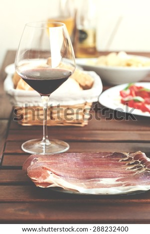 Prosciutto, red wine, mozzarella an tomatoes served on wooden table at balcony. Post processed with vintage filter. - stock photo
