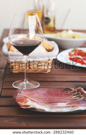 Prosciutto, red wine, mozzarella an tomatoes served on wooden table at balcony. Post processed with matte filter. - stock photo