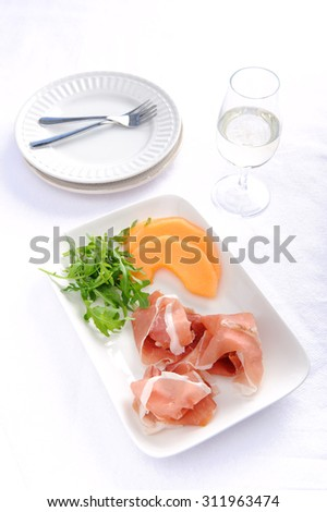 Prosciutto served with cantaloupe, a common Italian antipasto with a glass of wine  - stock photo