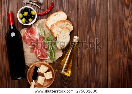 Prosciutto, wine, olives, parmesan and olive oil on wooden table. Top view with copy space  - stock photo