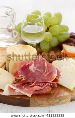 prosciutto with cheese and wine in wooden board