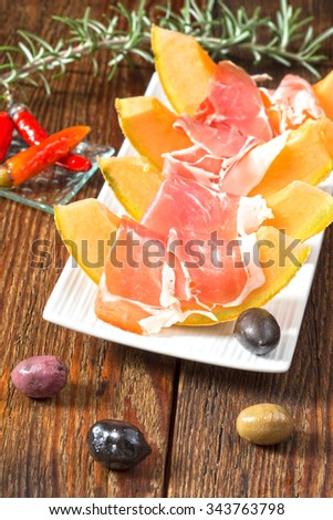 Prosciutto with melon, herbs and olives - stock photo
