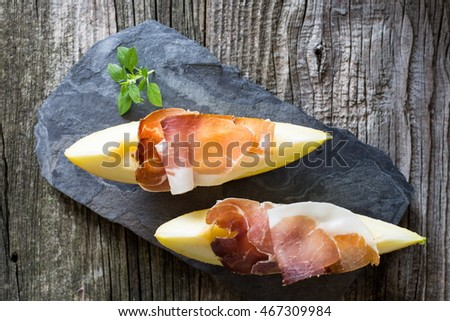 Prosciutto with melon served on a slate with rustic wooden table in the background top view