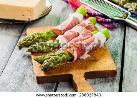 Prosciutto wrapped green asparagus on a cutting board