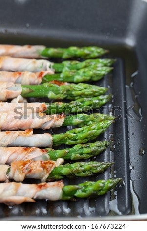 Prosciutto wrapped green asparagus on a grilling pan - stock photo
