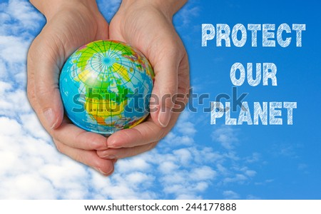 Protect our Planet - female hand with earth and blue sky in the background - stock photo