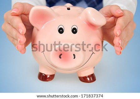 Protect piggy bank on blue background - stock photo