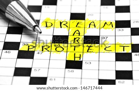 protect the earth! it's not just a dream. Written on a crossword and than marked with yellow text marker. - stock photo