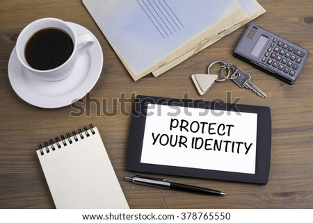 Protect Your Identity. Text on tablet device on a wooden table - stock photo