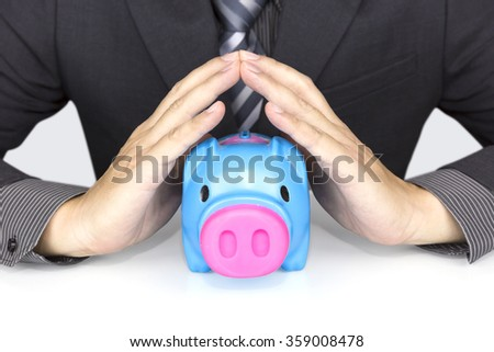 protect your savings - with his hands covering the piggy bank - stock photo