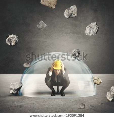 Protected businessman from the storm of falling rocks - stock photo