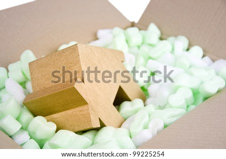 protecting your property, moving house, gold house in box full of foam protective packaging - stock photo