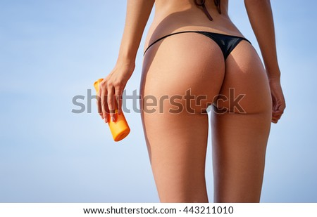 Protection and health care. Close up of sexy young woman in bikini holding sunscreen lotion. - stock photo