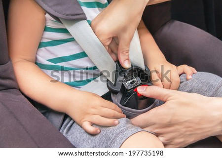 Protection in the car. Hands of caucasian woman is fastening security belt to child, who is sitting in safety car seat (chair). Toddler has a trip in summer day. Vehicle and transportation concept.  - stock photo