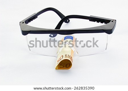 Protective goggles and fifty euro banknote in a white background - stock photo