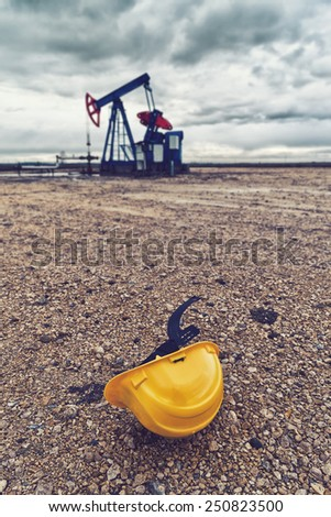 Protective Hardhat and Pumpjack Oil Pump operating on natural gas in the field pumping from the oil well. - stock photo