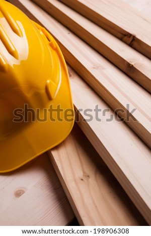 Protective helmet and new wooden planks. - stock photo