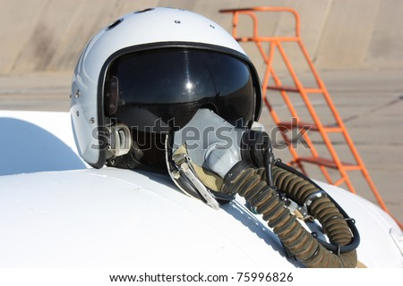 Protective helmet of the pilot against the plane with an oxygen mask on a fuel tank - stock photo