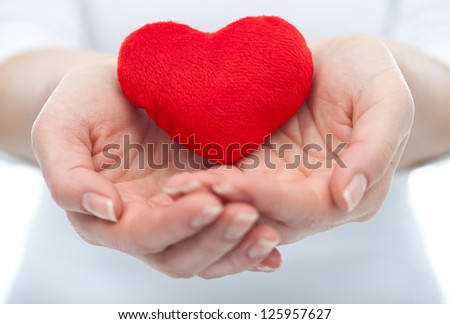Protective woman hand holding a red heart in her hands