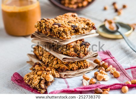 protein bars granola with seeds, peanut butter and dried fruit, healthy snack on wooden background - stock photo