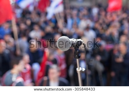 Protest. Public demonstration. Microphone in focus against blurred audience.