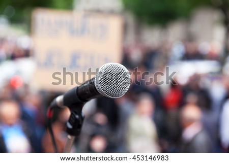 Protest. Public demonstration. Microphone in focus against blurred crowd. Political rally.