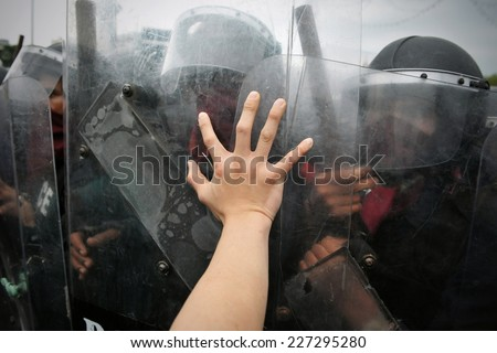 Protester Pushes Police Riot Shields at a Political Rally - stock photo