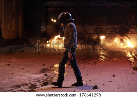 Protester with a fire extinguisher is on the background of a burning bus. Kyiv, Ukraine, January 19, 2014 - stock photo
